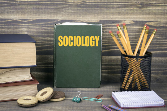 Sociology business concept. Book on a wooden background.