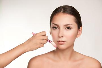 Make up artist do makeup girl. Brush near face. Professional at salon
