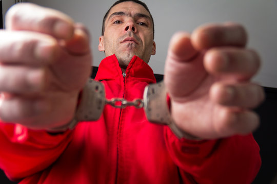 Criminal in handcuffs arrested for crimes.Close-up of a criminal hand in handcuffs. Frog perspective.