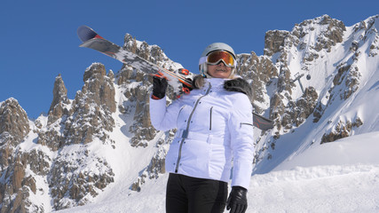 Woman skier with skis on her shoulder admires beauty of nature in the mountains