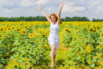 Candid red haired woman in white dress in the sunflowers at middle of a field in summer. Wellness concept, positive emotions and lifestyle.