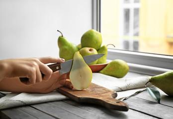 Woman cutting ripe pear on table, closeup