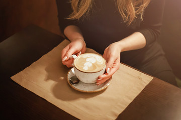 close-up in the cafe hands of a girl holding a Cup of coffee with a pattern (picture)