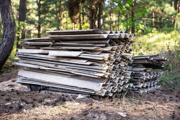 environment pollution - stack of old asbestos slate roof sheets in forest