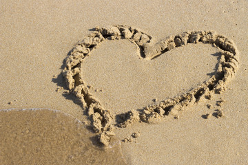 heart drawn on sand and sea, view from above