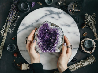 The witch is holding amethyst stone surrounded magic things. View from above.
