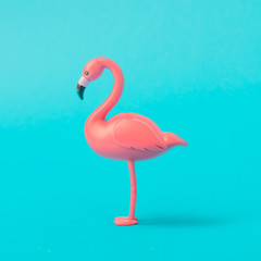 Pink Flamingo toy on pastel blue background. Minimal summer concept.