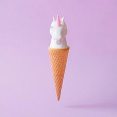 White painted unicorn head ice cream on pastel purple background. Minimal art fantasy concept. Summer fairytale.