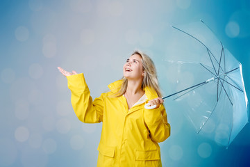 Blonde woman wearing yellow raincoat holding transparent umbrella checking weather if it is raining. Protected against rain and hurricane