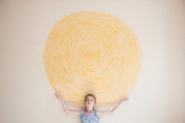 concept of beautiful caucasian girl holding sun painted on yellow wall indoors