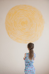 little pensive caucasian girl looking at yellow sun painted on wall indoors