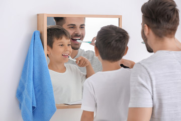 Fotomurales - Little boy and his father brushing teeth in bathroom