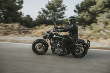 Man in black leather jacket riding a motorcycle on the road across the mountain.