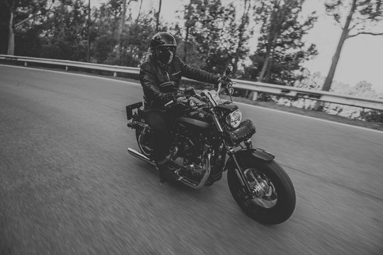 Black and white of man riding a classic motorcycle on the road.