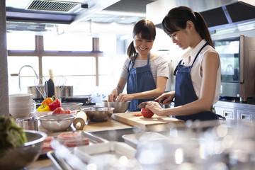 料理教室で友人と一緒に料理を作る女性二人