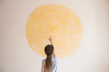 little girl pointing finger at yellow sun painted on wall indoors