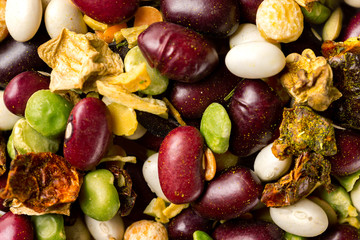 Macro image of beans and peas mix with dried eggplants with spices as natural vegan background.