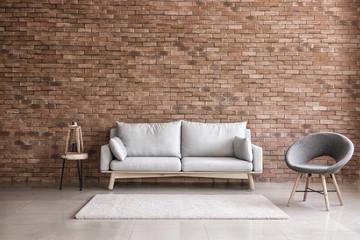 Fototapeta Modern interior of living room with comfortable sofa and armchair near brick wall obraz