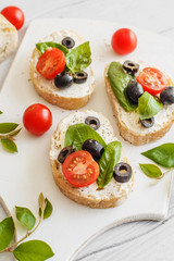 Sandwiches with cream cheese tomatoes, olives and basil on a wooden white board