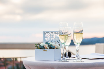 Wineglasses of ice champagne on table for wedding reception after wedding ceremony by the sea and sunset. Box with flowers with rings.