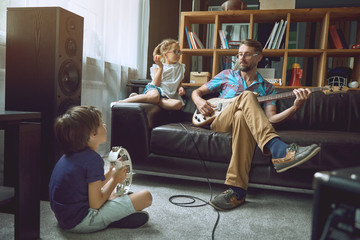 Children play with their dad on musical instruments.