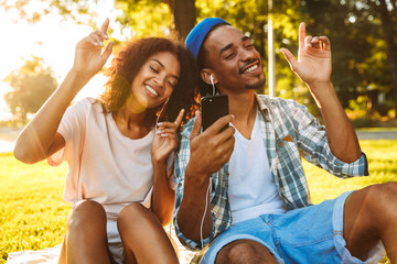 Portrait of a joyful young african couple in earphones