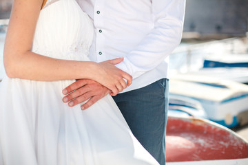 Couple are hugging after wedding ceremony. Man and woman are wearing in white clothes and gown. Bride is pregnant. Сoncept of harmony and trust.