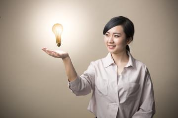 手のひらに電球を浮かべて微笑む若い女性