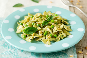 Pasta with pesto sauce, green peas and basil on a wooden table. Rustic style.