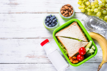 Lunch box with sandwich, vegetables, yogurt, nuts and berries.