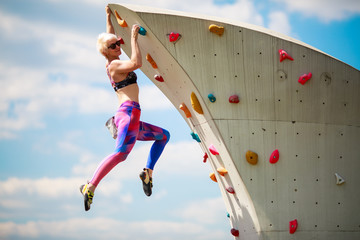 Photo from side of sports blonde in leggings hanging on wall for climbing against blue sky