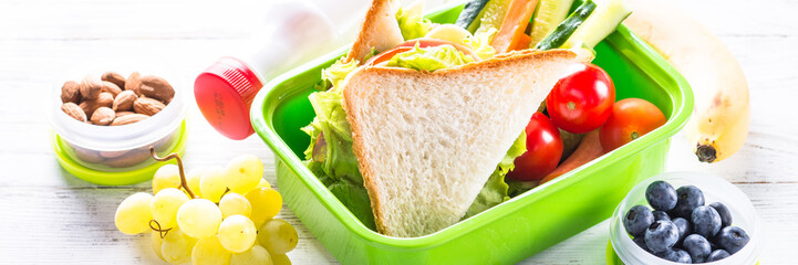 Photo sur Plexiglas Assortiment Lunch box with sandwich, vegetables, banana, water, nuts and ber