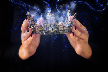 image of lady in black holding queen crown decorated with precious stones and magical glowing mysterious dust. fantasy medieval period. Black queen.