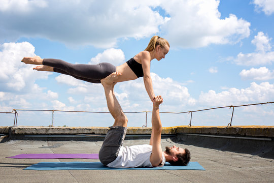 Man and woman are engaged in acro yoga