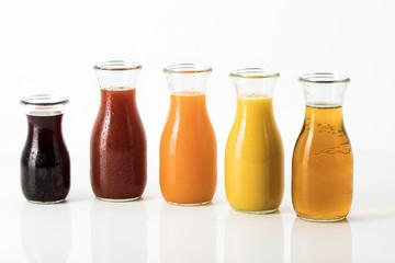 unterschiedliche Fruchtsäfte in Glasflaschen vor weissem Hintergrund, Freisteller