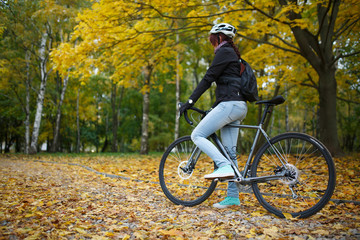 Photo of girl in helmet riding bicycle in autumn forest