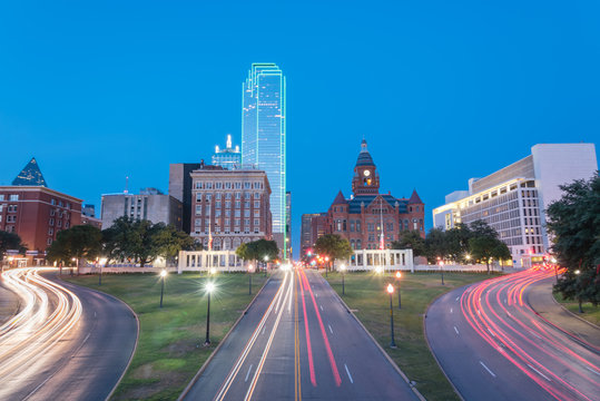 Dallas skyscrapers and light trail traffic over Dealey Plaza, JKF assassination site. Skyline and transportation cityscape at twilight