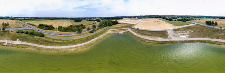 Panorama in high resolution, composed of photos with the drone, from the centre of a new rainwater retention basin to a new development and a country road