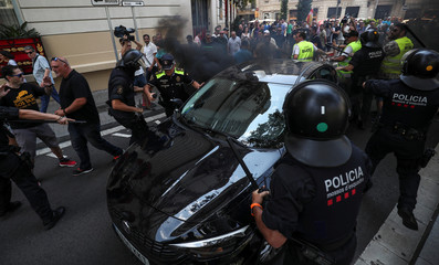 Catalan police in riot gear try to clear the way for a Uber car as skirmishes break out with taxi drivers during a taxi strike in Barcelona