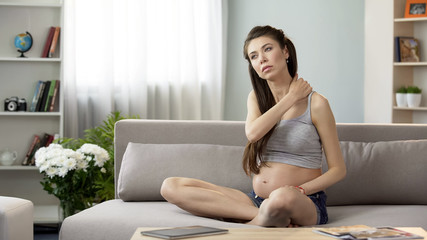 Pregnant female massaging strained neck and shoulders, tensed muscles problem