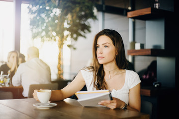 Portrait of a young, beautiful girl sitting in a cafe, drinking coffee, reading a paper, working, thinking, studying, enjoying.