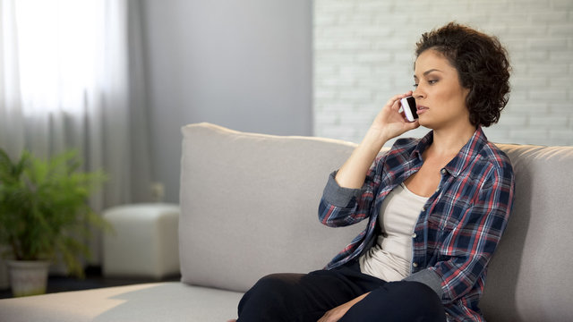 Beautiful woman talking on phone, having serious conversation, looking for job