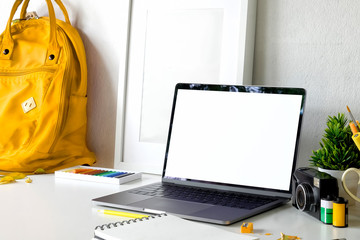 Photographer workspace with blank screen laptop on white desk.