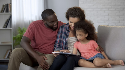 Parents showing daughter her first photos on tablet, cozy family atmosphere
