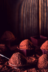 Chocolate truffles on wood, macro. delicious homemade truffle with dark chocolate and cocoa powder. Gourmet candies made by chocolatier on spiral dipping tool. Sweet dessert. Chocolaterie border