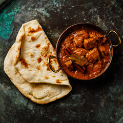 Chicken tikka masala spicy curry meat food and naan bread on dark background close-up
