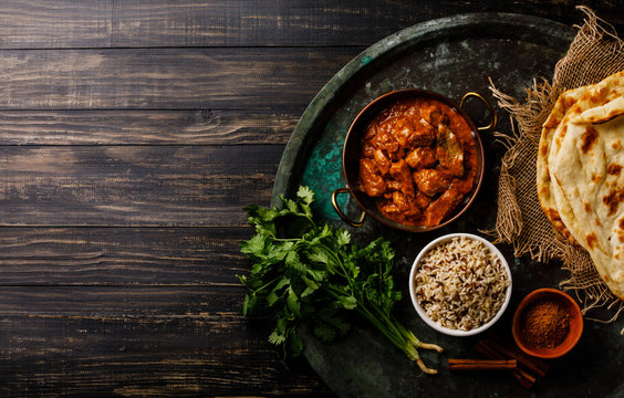 Chicken tikka masala spicy curry meat food with rice and naan bread on dark background copy space