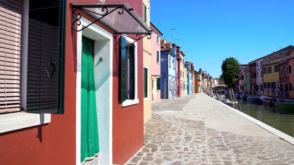 Beautiful street with multicolored houses in Burano attracting to walk, Venice