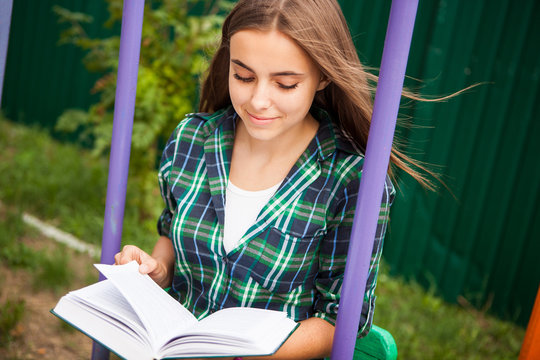 Beautiful student girl read book outdoors and smile, education or leisure concept