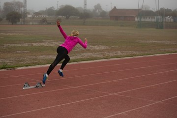 Female athlete running from starting block on the track
